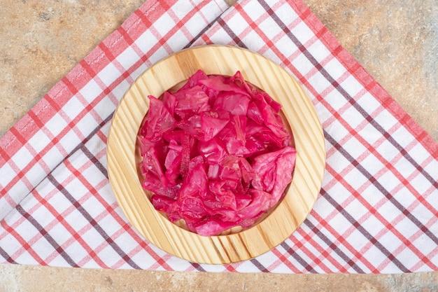 Cavolo rosso marinato sul piatto di legno.