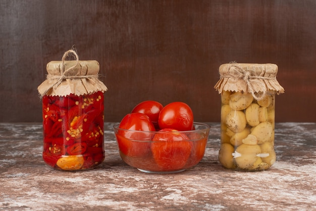 Pickled red peppers and mushrooms in a glass jar on marble table with bowl of pickled tomatoes.
