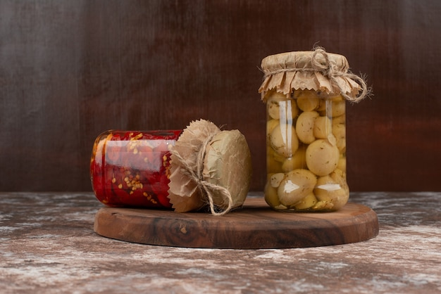 Pickled red peppers and mushrooms in a glass jar on wooden plate.