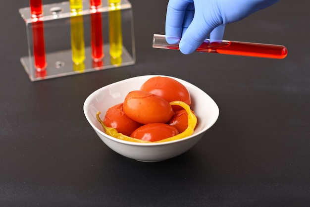 Pickled red tomatoes with chilli and laboratory glass with red liquid how the food is colored.