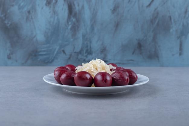 Crauti sott'aceto e prugna sul piatto, sullo sfondo di marmo.