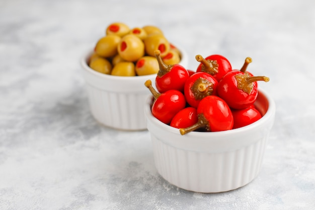 Pickled small round red hot cherry chili peppers on grey concrete