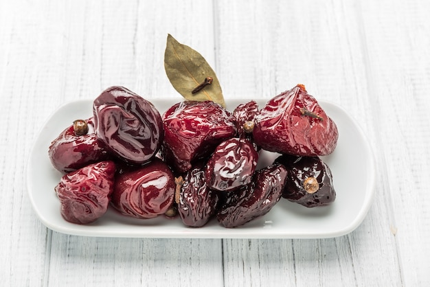 Pickled spicy plums in vinegar-based marinade with herbs