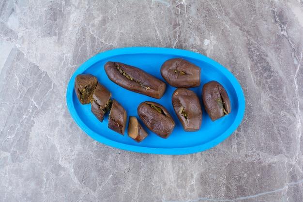 Маринованные фаршированные баклажаны на синей тарелке.