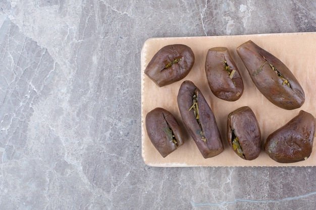 Маринованные фаршированные баклажаны на деревянной доске.