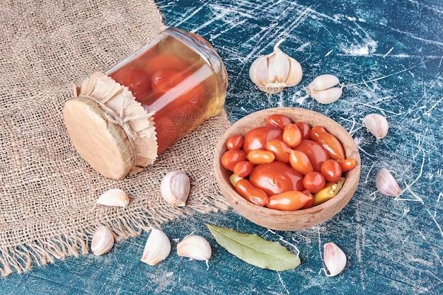Pomodori marinati in vaso di vetro e ciotola con aglio sul blu.