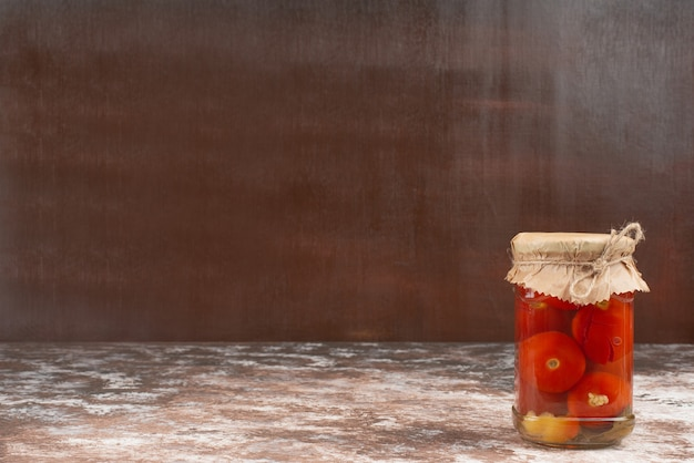 Pickled tomatoes in glass jar on marble table.