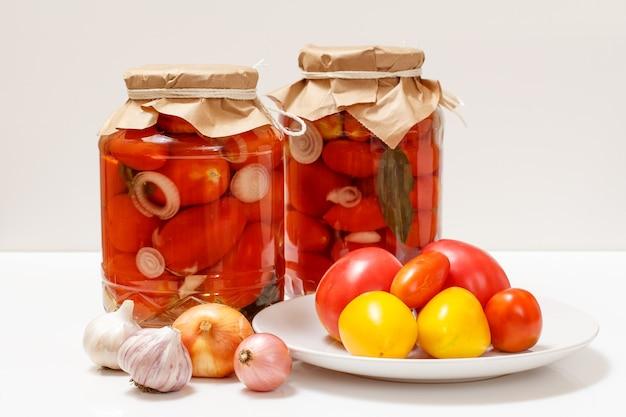 흰색 바탕에 유리 항아리에 절인된 토마토입니다.