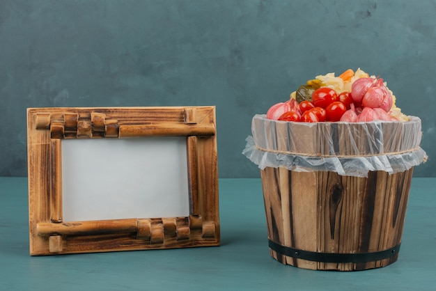 Pickled tomatoes, olives, garlic, cabbage, cucumbers in wooden bucket with picture frame.