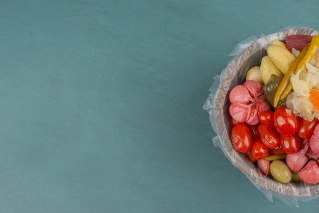 Pickled tomatoes, olives, garlic, cabbage, cucumbers in wooden bucket.