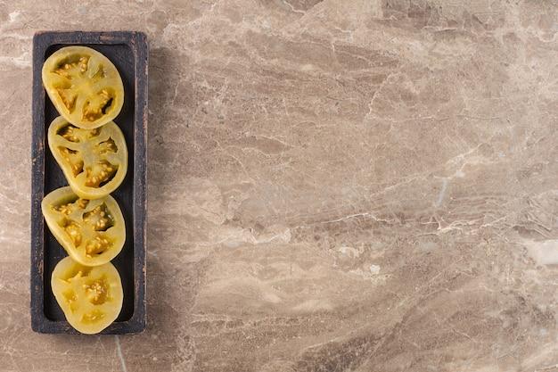절인 토마토는 돌 테이블에 배치됩니다. 무료 사진