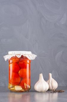 石のテーブルに置いた新鮮なニンニクとトマトのピクルス。