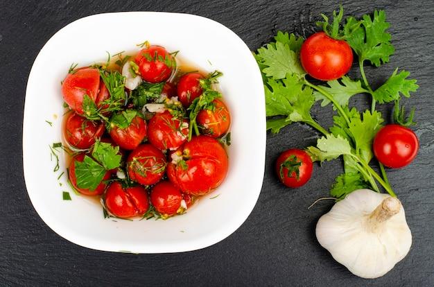 허브와 마늘을 곁들인 절인 토마토. 스튜디오 사진.