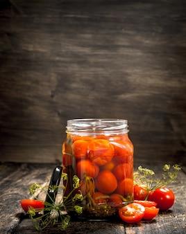 瓶にハーブとスパイスを入れたトマトのピクルス。