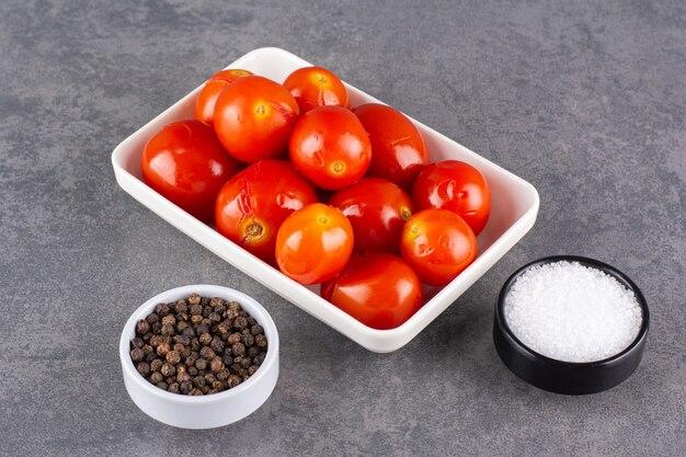 후추 옥수수와 절인 토마토는 돌 테이블에 놓습니다.