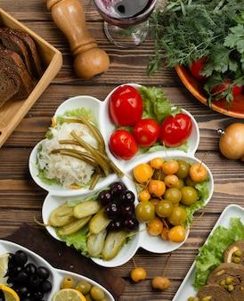 Маринованная овощная тарелка с помидорами, солеными огурцами, капустой