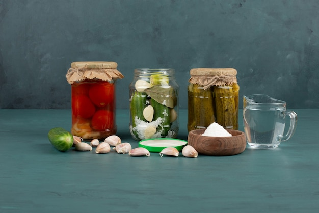 Pickled vegetables in glass jar and salt bowl on blue surface with fresh garlic.