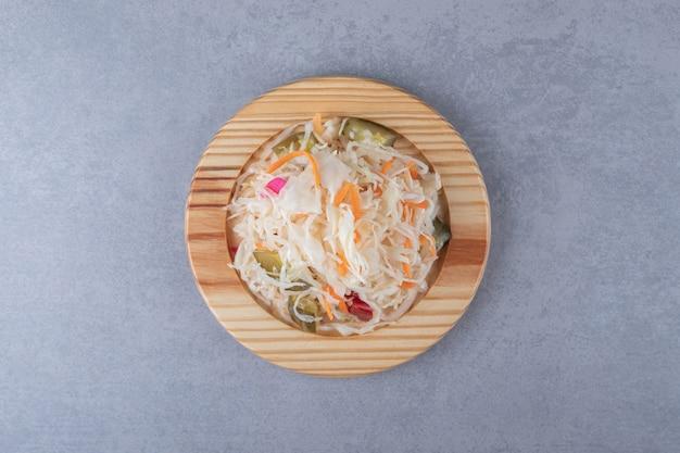 Mix di verdure sott'aceto nel piatto di legno