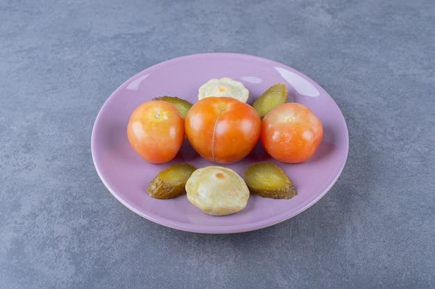 紫の皿に漬けた野菜。きゅうりのスライスと緑のパティパンスカッシュと赤いトマト。