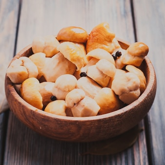 黒胡椒と月桂樹の葉を木製のボウルに入れて漬けた白いポルチーニ