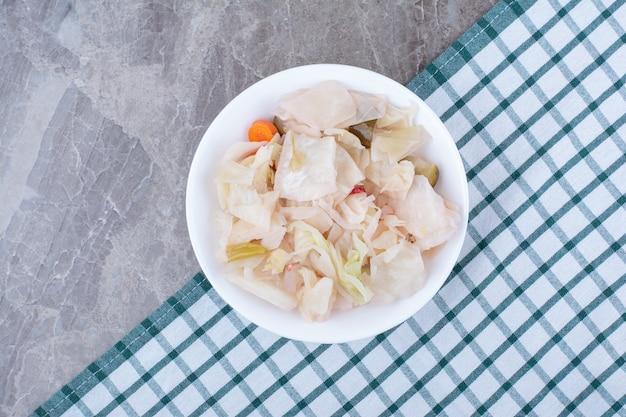식탁보와 흰 그릇에 절인 된 흰 양배추.