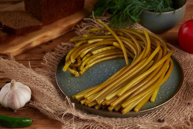 Маринованный дикий чеснок на тарелке на деревянном
