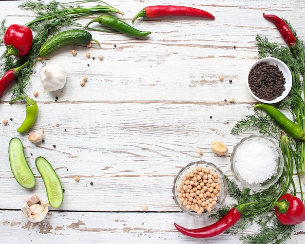 Pickles background on white wooden table with green and red and chili peppers, fennel, salt, black peppercorns, garlic, pea, close up, healthy concept, top view, flat lay
