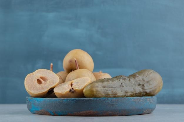Cetrioli e mele sottaceto su piatto di legno