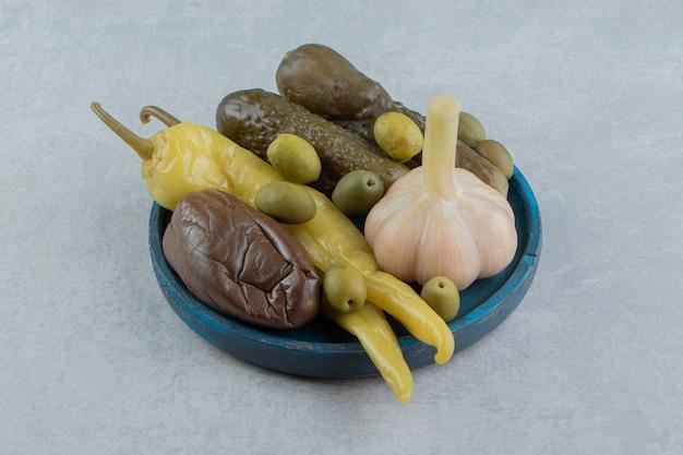 大理石の表面の木板に唐辛子、オリーブ、きゅうり、なすを漬ける