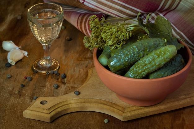 Соленья в глиняной посуде и стакан водки в винтажном стиле традиционная русская закуска к водке