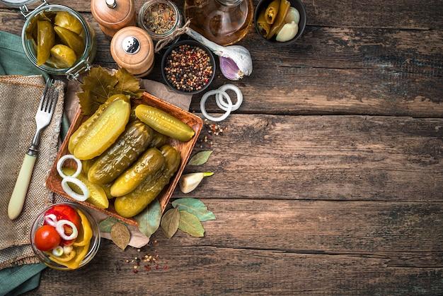 Соленья, лук, чеснок, специи, льняные салфетки на деревянном фоне. концепция домашних солений.