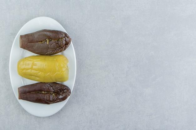 Соленья перец и баклажаны на тарелке