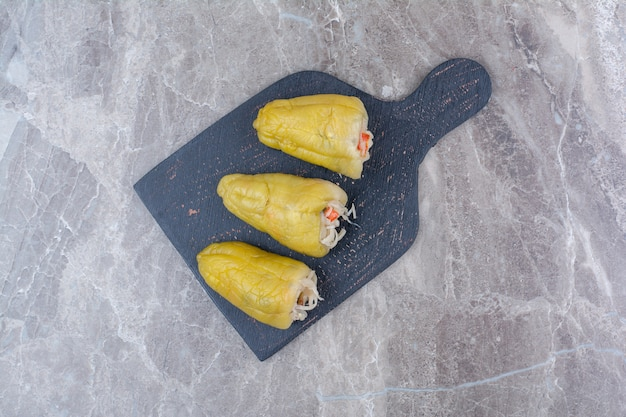 Pickles stuffed into peppers on dark board.