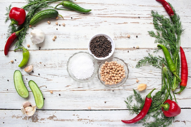 Pickles on white wooden table with green and red and chili peppers, fennel, salt, black peppercorns, garlic, pea, close up, healthy concept, top view, flat lay