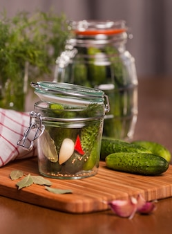 Pickles with garlic in glass jar on cutting board