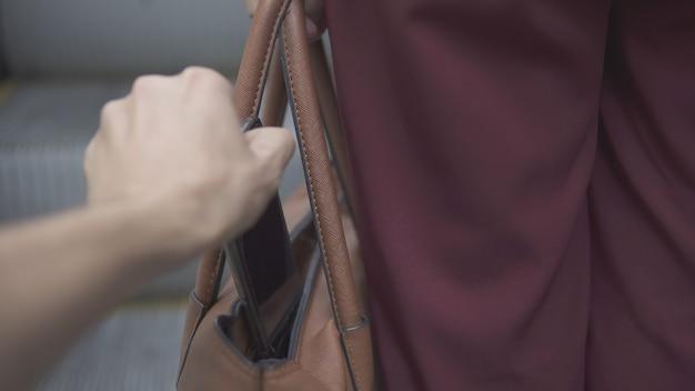 소매치기가 주황색 핸드백에서 스마트폰을 훔치고 있습니다. 선택적 초점