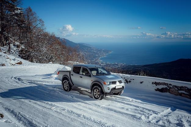 Пикап на дороге, красивая зимняя дорога под снежными горами. блестящий серебристый грузовик измеряет глубину снега. идея и концепция свободы передвижения в любую погоду