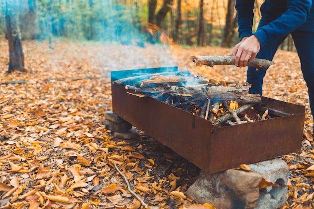 ピクニック。男がグリルに丸太を投げます。背景の秋の森。閉じる。
