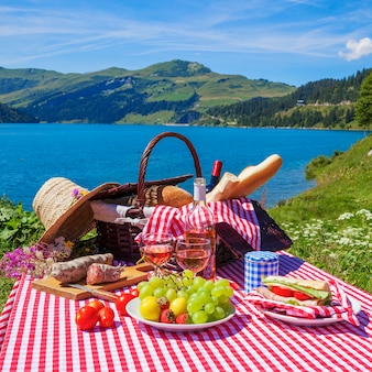 Picnic in alpine mountains with lake on background, panoramic view