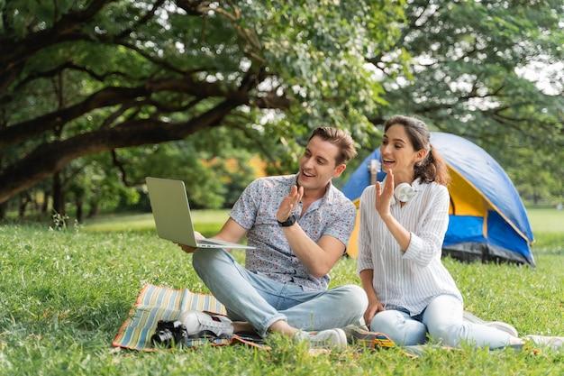 피크닉 및 캠핑 시간. 재미 있는 젊은 부부는 공원에서 노트북과 캠핑을 사용합니다. 사랑과 부드러움, 그의 여자 친구에게 기타를 연주하는 낭만적인 남자, 라이프 스타일 개념
