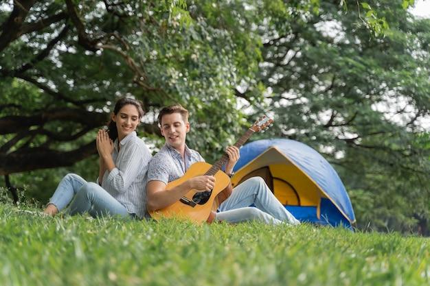 피크닉 및 캠핑 시간. 피크닉에서 기타와 함께 즐거운 시간을 보내는 젊은 부부와 공원에서 캠핑. 사랑과 부드러움, 그의 여자 친구에게 기타를 연주하는 낭만적인 남자, 라이프 스타일 개념
