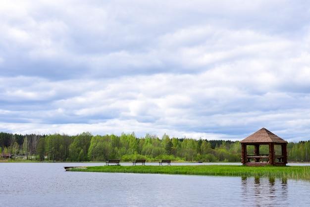 森の湖の岸にベンチとピクニックアーバー