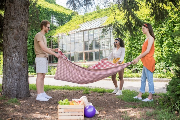 Picnic area. tall smiling guy and two long-haired girls standing thinking with blanket in hands in park on sunny day