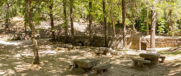Площадка для пикника с каменными столами и стульями, чтобы посидеть в природном парке.