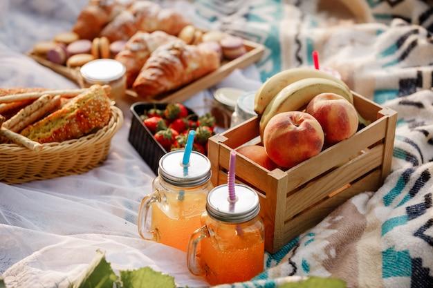 公園でのピクニック。新鮮な果物、氷の冷たいスパークリングドリンク、夏の暑い日のクロワッサン。ピクニックランチ。セレクティブフォーカス