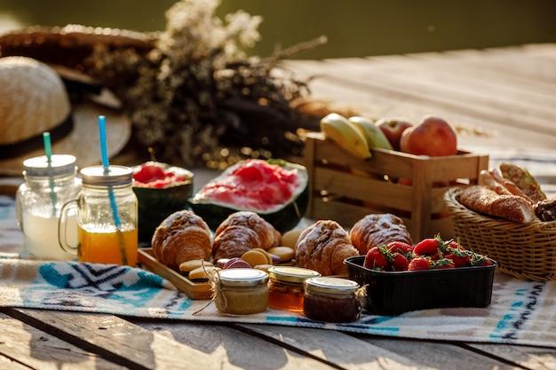 公園でのピクニック。新鮮な果物、氷の冷たいスパークリングドリンク、夏の暑い日のクロワッサン。ピクニックランチ。