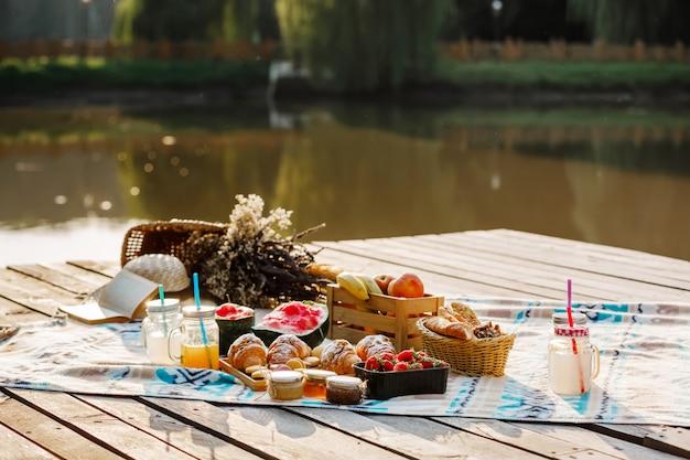 湖の近くの公園でのピクニック。新鮮な果物、氷の冷たいスパークリングドリンク、夏の暑い日のクロワッサン。ピクニックランチ。セレクティブフォーカス