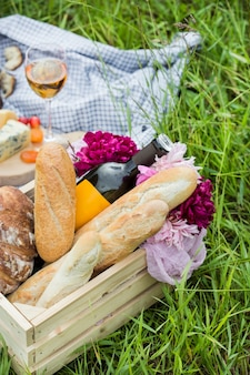 芝生の上の公園でのピクニック:ワイン、チーズ、パン