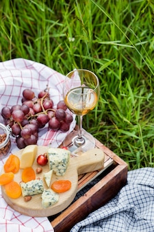 Пикник в парке на траве: вино, сыр и хлеб