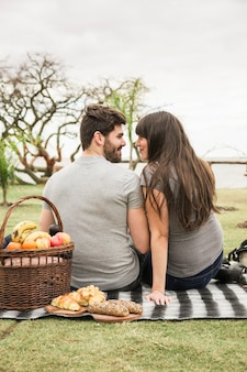 Picnic basket and baked bread in front of young couple looking at each other